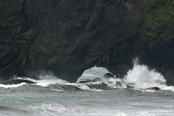 North Atlantic wave crashing into the volcanic rock at one of the sea archs of Dyrhólaey (Door Hill Island).