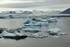 Jökulsárlón (lagoon) - displaying the glacial ice afloat, calved from the distal glacier of the Breiðamerkurjökull - adjacent the western end and steep slope of the Veðhurárdalsegg (ridge) - with distal the Esjufjöll (mountains), a nunatak (glacial rock Island).