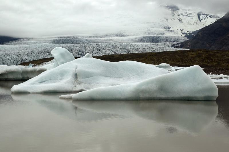 Iceberg reflection upon the glacial flour water of the Fjallssárlón (lagoon) - beyond the glacial till moraine, to the Fjallsjökull (glacier) flowing between the Ærfjall and Breiðamerkurfjall (mountains).