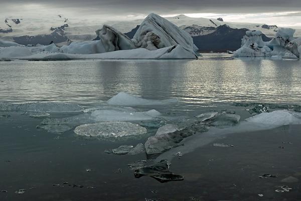 Growler drifted near the rocky shoreline along the Jökulsárlón (lagoon), with icebergs beyond - and distal is the Múli (mountain), Hrútárjökull (glacier), Ærfjall (mountain), Fjallsjökull (glacier) - Breiðamerkurfjall (mountain), Þuríðhartindur (peak), Mikill (rock island), Breiðamerkurjökull (glacier), and the Fjölsvinnsfjöll (mountains) - here during late June, under a densely clouded sky.