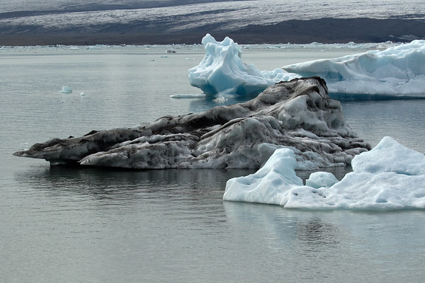 Jökulsárlón (lagoon) - with icebergs afloatm one significantly cloaked with glacial till - with beyond the Breiðamerkurjökull (glacier).