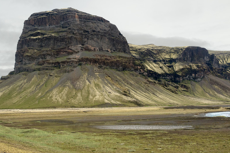Mount Lómagnúpur (peak) - along its southern end, which peaks at around 2,257 ft. (688 m), then above distal to its summit rising to around 2,507 ft. (764 m), the sea cliff in Iceland - located along the eastern boundary of the Katla UNESCO Global Geopark - at the southeasternmost area, of the Southern region in Iceland.