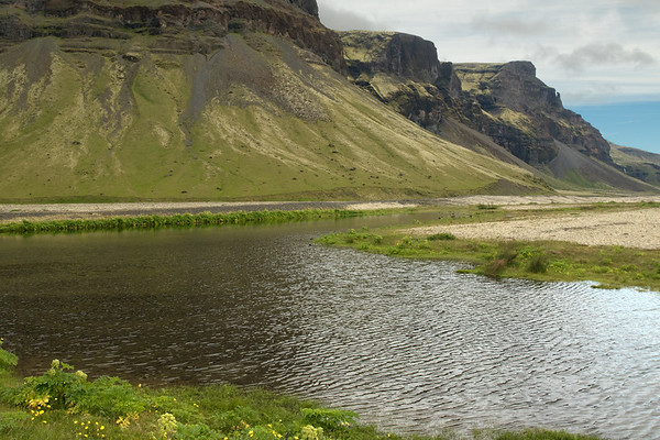 Across a glacial moraine formed pond - to the southern slope and cliff face of mount Lómagnúpur (peak), then along its eastern cliff faces and ridges, to a distal ribbon falls dropping from the volcanic rock ledge - Southern region of Iceland.