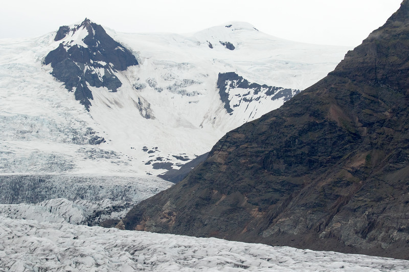 Across the Fjallsjökull (Mountain Glacier) - beyond the lower volcanic rock slope of the Breiðamerkurfjall (mountain) - to the jagged slopes and spire peak of the Antafjallstindur - and distal above at around 5,167 ft. (1,575 m) is the Káratindur (peak), amongst the snow cloaked glacial ice - Eastern region of Iceland.