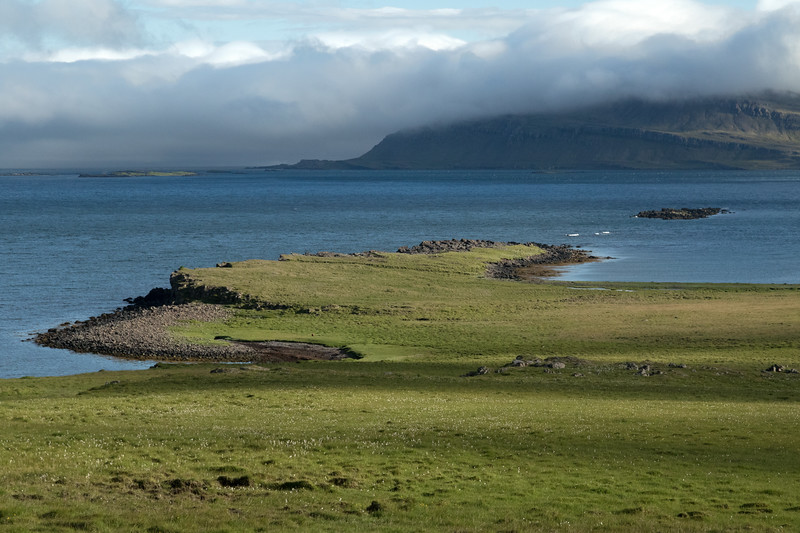 Along the mostly grassland covered slope down to the Réttartangi (point) - out to the waves breaking upon the Breiðdalsfjörður (Wide Valley Fjord), adjacent the Axarsker (island) - with beyond the vegetated island of Hafnarey, then (r) the  the Spaðhólmi (island) and directly beyond is the slope of the Skoruhjalli, below the cloud bank, at the southern end of the fjord.