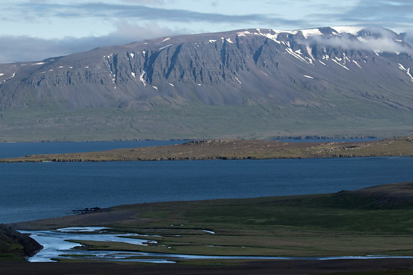 From the cloud-shadowed Króklækur (stream) flowing into the Nípsfjörður (fjord) - to the narrow peninsula of Kolbeinstangi - beyond the Vopnafjörður (fjord) - then the clouds and snow banks along the Krossavíkurfjöll (mountains) - Eastern region of Iceland.