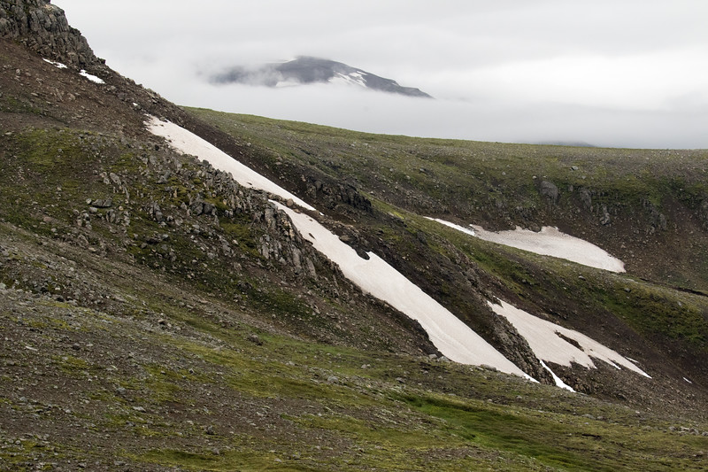 Across the lower northern slope along the Seldalsfjall (mountain), amongst the snow banks - distal beyond the clouds, to the slope along the Blafjall (mountain) - Eastern region of Iceland.