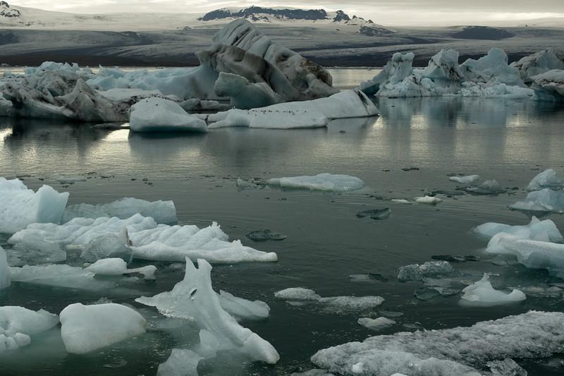 Jökulsárlón (Glacier River Lagoon) - displaying the calved glacial ice afloat - with beyond the Breiðamerkurjökull (glacier) and the edge of the Fjölsvinnsfjöll (mountains) - Eastern region of Iceland.