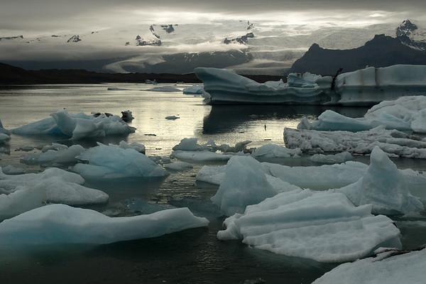 Jökulsárlón (Glacier River Lagoon), with the cloud shadowed icebergs, bergy bits, and growlers afloat - beyond to the sunlight patch striking the Hrútárjökull and Fjallsjökull (glaciers) flowing between the Múli, Ærfjall, and Breiðamerkurfjall (mountain).