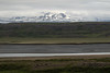 Across the Jökulsá Brú (river) - and the slopes along the headland of the  Hróarstunga - to distal amongst the clouds and snow banks, the Beinageitarfjall (mountain) - Eastern region of Iceland.