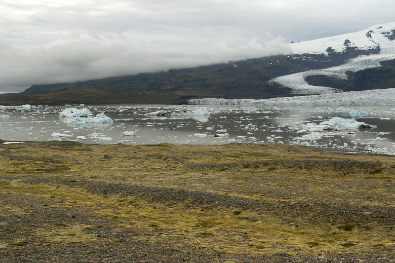 Across the terminal till and down to the Fjallssárlón (Mountain Lagoon) - with beyond the terminus snouts of the Fjallsjökull and Hrútárjökull (glaciers) - and distal amongst the clouds the lower slope along the central volcano of the Öræfajökull.