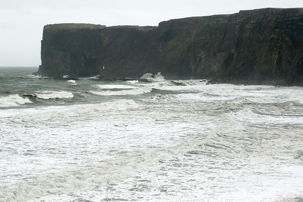 North Atlantic waves breaking and crashing along the Dyrhólaey (Door Hill Island) - which was an island until the lava flows and a glacial outwash plain sealed its western area - now it has the geographical distinction of the southernmost point of mainland Iceland.