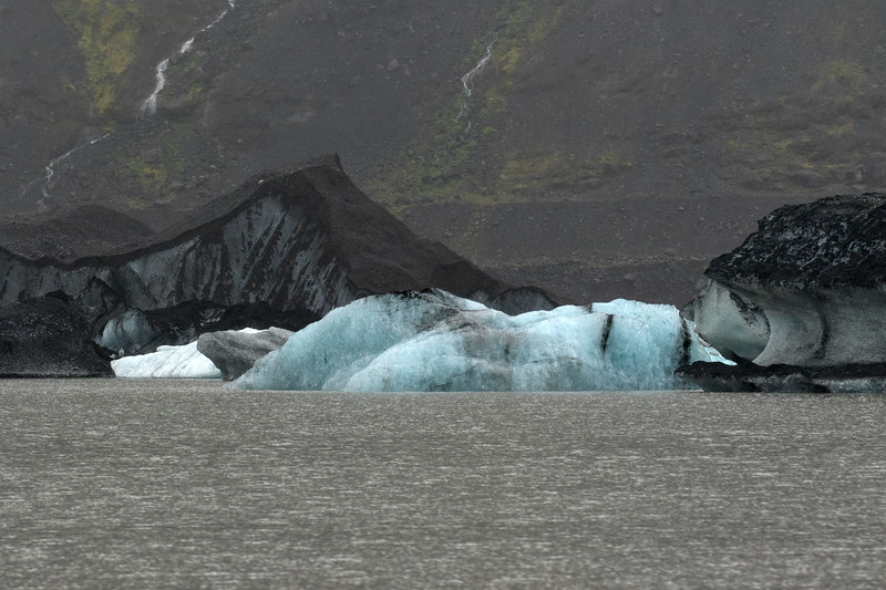 Glacial Ice - emits a blue visible light because the air has been compressed and squeezed from glacial ice, thus resulting in larger ice crystals - therefore, when the electromagnetic radiation from the sun reaches its surface, the longer wavelength visible light (towards the infrared spectrum, visible red light) is absorbed, whereas the shorter visible light (towards the ultraviolet spectrum, visible blue light) is reflected and scattered.