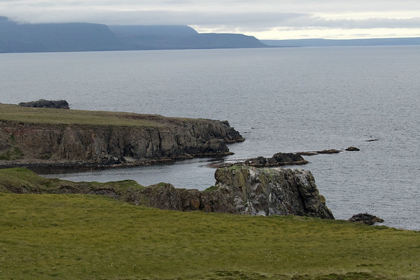 From the steep volcanic rock cliff along the Sjónarhóll (hill), at Skarfatangi (point), which forms the western end of the Bakkafjörður (fjord), in the Eastern region of Iceland - across the Bakkaflói (bay) - to the Langanes (peninsula), from the Selfjall, Storafjall, and Bæjarfjall (mountains) amongst the clouds, to the distal northeastern area - located in the Northeastern region of Iceland.