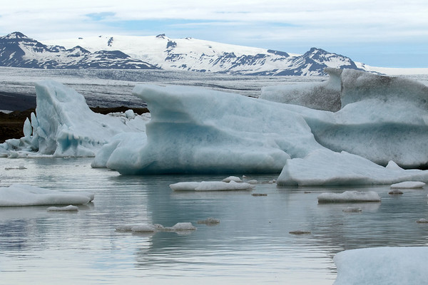 Fjallssárlón (lagoon) displaying its glacial ice, calved from the Fjallsjökull (glacier) - beyond the Breiðamerkurjökull (glacier) - and distal the jagged slopes and peaks cloaked with glacial ice and snow, the glacial rock islands (nunatak) of the Esjufjöll (mountains).