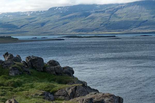 From the rocky southern cliff of the Breiðdalsfjörður (Wide Valley Fjord), clustered with grass, herb, and lichen - out to the Gunnhildarey (island) amongst several islets - and beyond to the snow patches and cloud bank along its northwestern slopes.