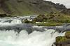 A cascade falls along the Fossalar (river) and the Brunahraun (lava field) - above the basaltic rock along the Þverárfjall (mountain).