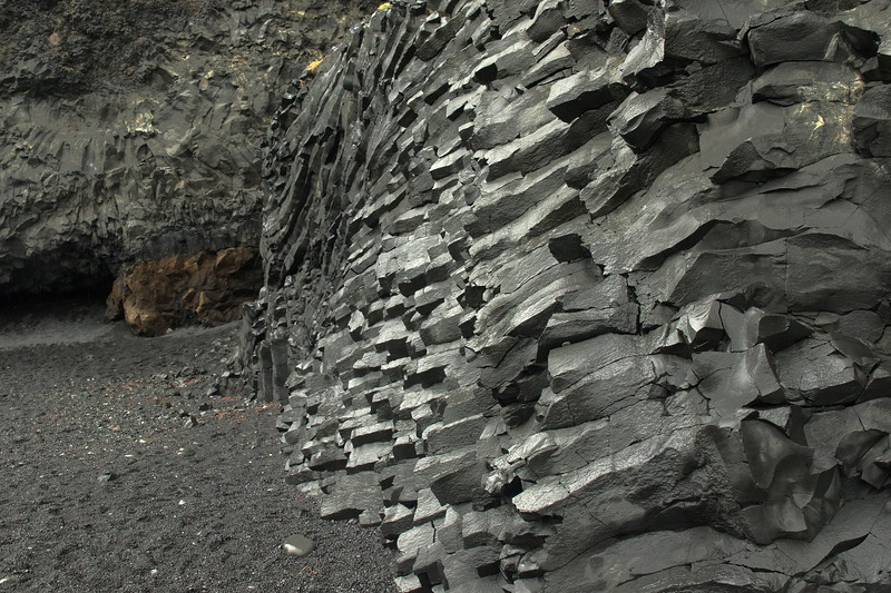 "Polygonal columnar jointing - (having numerous straight line segments) -  here specifically an ""entablature facies"" where the formation displays less regular columns, which typically have curving sides - here along the Reynisfjara (beach)."