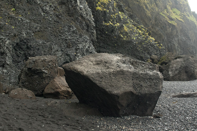 Reynisfjara (beach) - where the smooth water-eroded igneous rock stones meet the sand and fallen tallus boulders from the southern slope of the Glydarölll (hill), with lithophytic vegetation thereupon - a rainy day in late June.