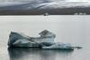 Calved icebergs afloat the Jökulsárlón (lagoon) - beyond the lateral moraine slope, to the Breiðamerkurjökull (glacier), displaying its medial moraine atop.