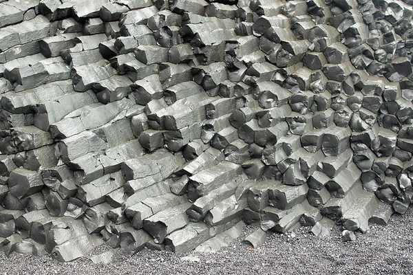 Horizontal polygonal columnar jointing of volcanic basalt rock - meets the sea eroded clasts of igneous rock - here along the Reynisfjara (beach) - Southern region of Iceland.
