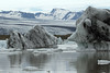 Calved glacial ice atop the Fjallssárlón (lagoon) - beyond across the Breiðamerkurjökull outlet glacier, to the volcanic rock slopes and ridges along the glacial rock islands of the Esjufjöll (mountains).