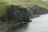 Vindhælisstapi (bluffs), displaing its columnar jointed basaltic rock - adjacent the eastern area of the Skagafjörður (fjord) - during a competely overcast and rainy day.