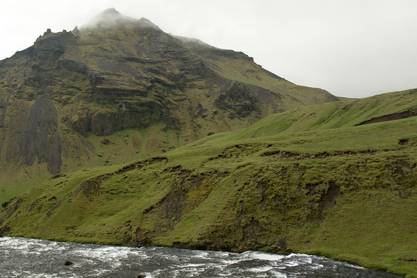 Across the glacial water of the Skógá (river), just above the Skógafoss (waterfall) - to the distal volcanic rock of the Drangshlíðharfjall (mountain), with the Daltindur (summit) up in the clouds rising to around 1,570 ft. (478 m) - southeastern area of the Eyjafjallajokull (volcano) - Southern region of Iceland.