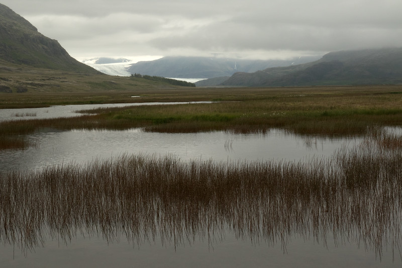 Across the wetland of the Hornafjarðarfljót (river) - beyond the Viðborðsfjall (mountain) - to the Múlafoss (falls) flowing along the Núpar (mountain), adjacent the Hoffellsjökull (glacier) - Eastern region of Iceland.