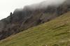 Craggy volcanic rock ridge amongst the clouds, below the Heiðarhnjukúr (peak).