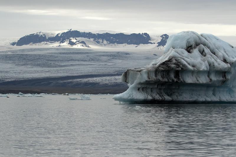 Jökulsárlón (Glacier River Lagoon) - from the glacial till cloaked iceberg - to the glacial till medial moraine known as the Svartarönd (Black Stripe), here atop the Breiðamerkurjökull (glacier) - and distal to a sunlight patch upon the volcanic rocks at the Mávabyggðir.