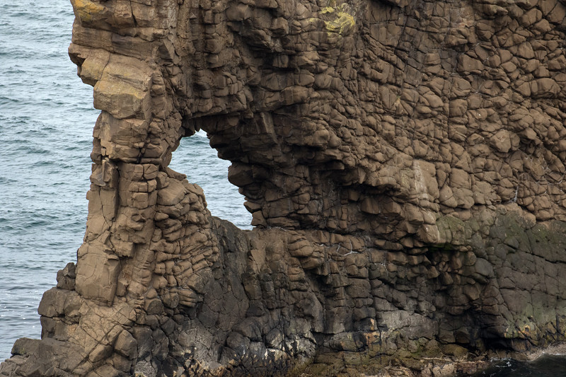 Thru the eroded volcanic rock sea arch - to the water upon the Vopnafjörður (fjord).