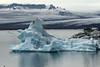 Weather sculpted iceberg afloat the Jökulsárlón (lagoon) - ice stream of the Breiðamerkurjökull (glacier) - volcanic rocks at the Mávabyggðir.