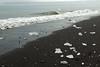 Glacial ice, black igneous sand, volcanic stones, breaking wave of the North Atlantic - Diamond Beach.
