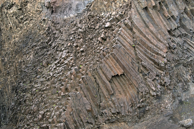 """Polygonal columnar jointing (having numerous straight line segments) - here specifically an """"entablature facies"""" where the formation displays less regular columns, which typically have curving sides - located along the Hengifossgljúfur (gorge)."""