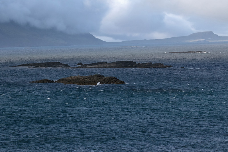 Beyond the wave crashing into the islets, along the mouth of the Breiðdalsfjörður (Wide Valley Fjord) - to the sunlight patch upon the distal Kambanes (peninsula), and adjacent amongst the clouds is the slope of the Mosfell (mountain) - Eastern region of Iceland.