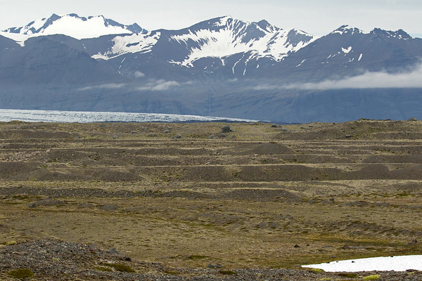 From the lateral moraine along the Breiðamerkursandur (sand plain) adjacent the edge of a glacial formed endorheic lake - to the edge of the Breiðamerkurjökull (glacier) - with above a waterfall flowing down the slopes of the Fremri-Veðhurárdalur (front valley), with above the Veðhurárdalsegg (ridge) rising to about  3,280 ft. (1,000 m) - and distal (l) to the Veðhurárdalskambur (ridge top) peaking at around 3,655 ft. (1,114 m), and (r) amongst the cloud bank the Hellrafjall (mountain) reaching to near 3,105 ft. (946 m).
