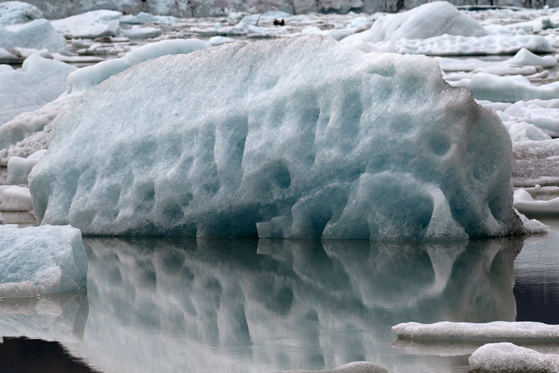 Weather eroded and sculpted glacial ice reflections upon the Fjallssárlón (Mountain Lagoon).