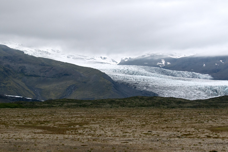 Fjallsjökull, an outlet glacier flowing from the Vatnajökull, the largest ice cap in Iceland, with an ice area of about 3,010 mi² (7,800 km²), and by volume the largest in Europe, measuring about 768 mi³ (3,200 km³), and averaging around 1,300-1,640 ft. (400-500 m) thick, and its deepest about 3,115 ft. (950 m) - here flowing betwen the Ærfjall and Breiðamerkurfjall (mountains) - with the thick cloud-cap above.