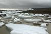 Growlers, bergy bits, and icebergs adrift the Fjallssárlón (Mountain Lagoon) - beyond the glacial till moraine, to the cloud bank amongst the eastern slopes of the Öræfajökull (volcano).