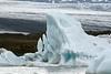 Weather sculpted iceberg afloat the Fjallssárlón (lagoon) - with beyond the terminal moraine (glacial deposited till), then the glacial ice stream  along the Breiðamerkurjökull (glacier).
