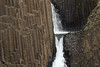 Litlanesfoss or Stuðlabergsfoss (Basalt Column Falls) - the shorter upper falls, and upper crest of the larger lower falls - framed with the columns of igneous basalt rock - along the Hengifossá (river).