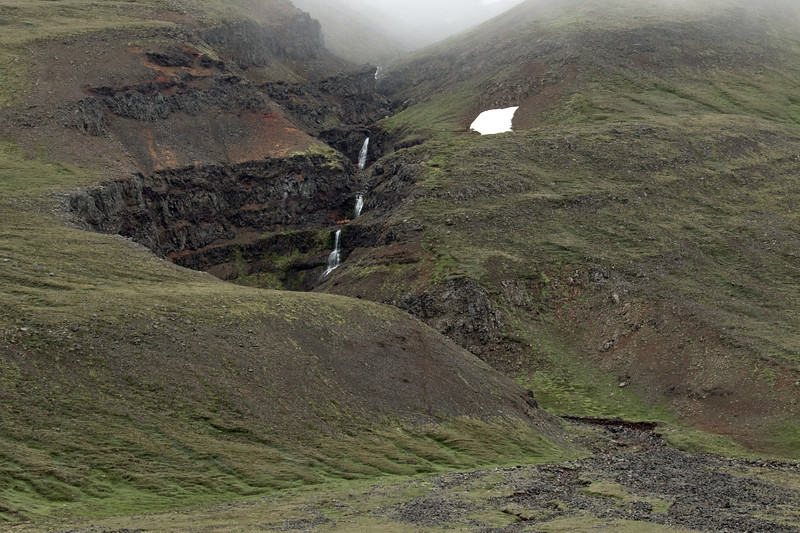 Cascading falls adjacent a solo snow-patch, late July, along the southern slope of the Reykjafjall (mountain) and amongst the clouds - Northwestern region of Iceland.