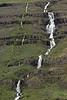 Cascading waterfalls descending along the lower slope of the Strandarfjall (mountain).