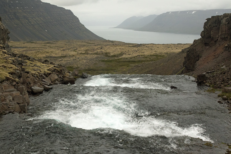 Over the crest of a falls along the Dynjandisá (river) at about 950 ft. (290 m), among the volcanic rock and moss vegetation - beyond to the slope of the Urdarfell (mountain) and below the Arnarfjörður (fjord), with distal the glacial slopes of the Slettanes (peninsula) - Westfjords region of Iceland.
