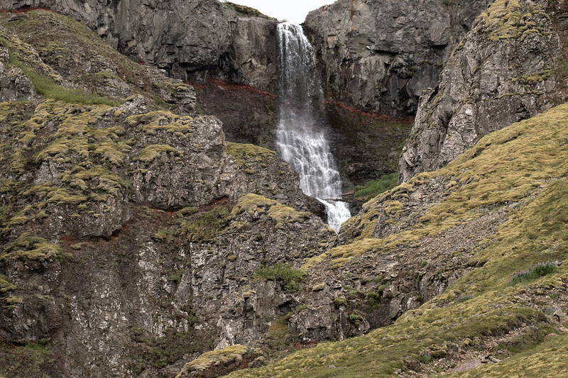 Cascade falls descending from the volcanic basalt rock ledge, amongst a thin strata of iron oxide - here along the slope of the Skápadalsmúli  Mountain - the eastern end of the Osafjörður (fjord) - Westfjords region of Iceland.