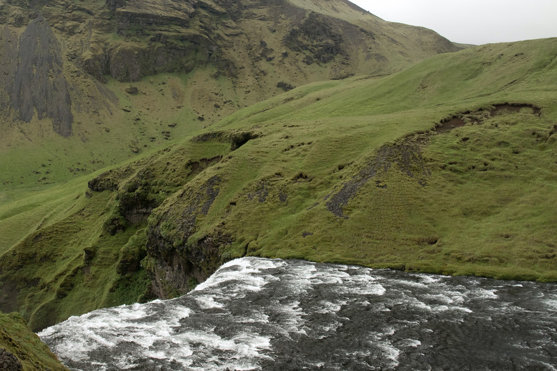 Skógafoss - across its crest of about 80 ft. (24 m), sourced by the Skógá River - to the distal northeastern slope of the Drangshlíðarfjall (mountain) - Southern region of Iceland.