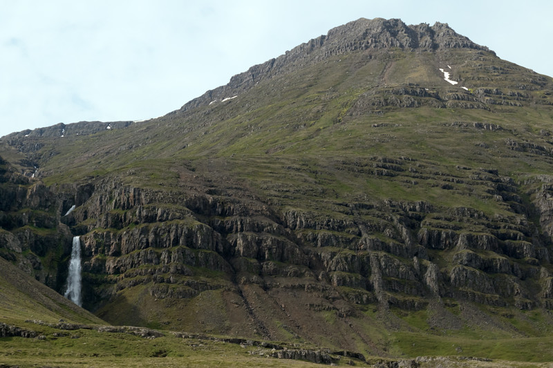 Hrútá (river) Falls - adjacent the eroded volcanic rock slope of the Hádegisfjall (mountain) - southwestern area of the Reydarfjörður (fjord) - Eastern region of Iceland.