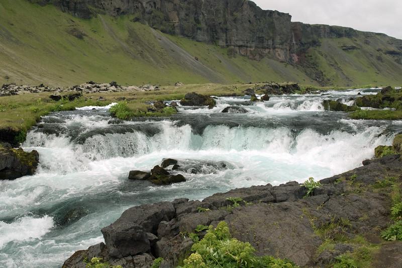 A cascade falls along the Fossalar (river) and the Brunahraun (lava field), with the extrusive basalt cliff along the Þverárfjall (mountain) beyond - Katla Geopark - Southern region of Iceland.