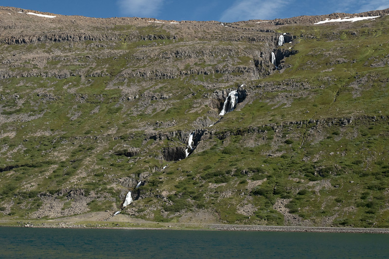 A cascading falls along the lower slope of the Valahnúkur (mountain), and a few snow matches along the ridge - descending into the southern area of the Hestfjörðurr (fjord) - Westfjords region of Iceland.